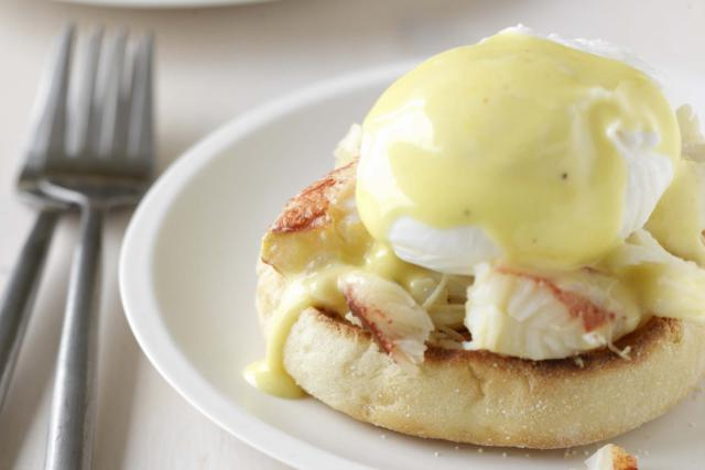 Eggs benedice over lump crab meat on an english muffin on a white plate