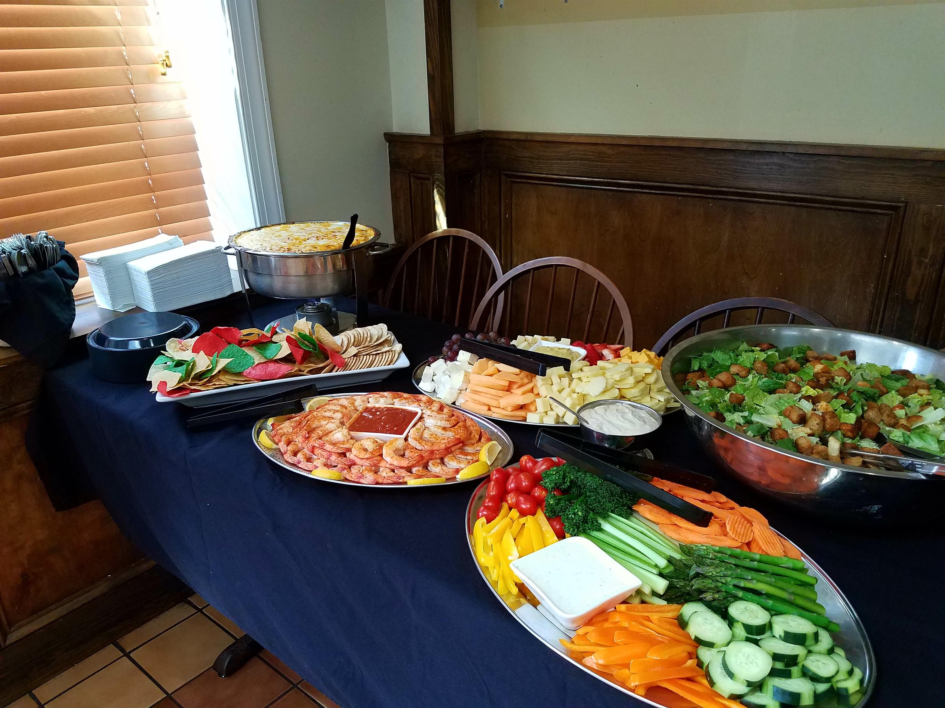 Catering table with blue table cloth topped with shrimp cocktail and vegetable platters