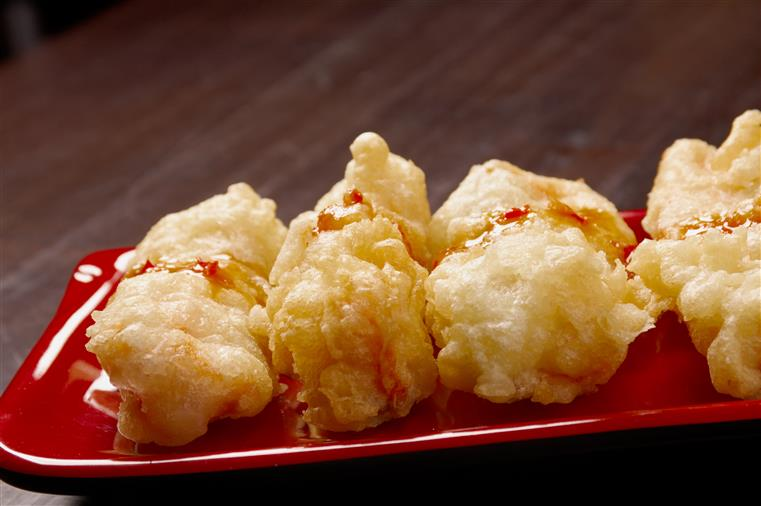Fried crab wontons on a red plate with sauce drizzled over