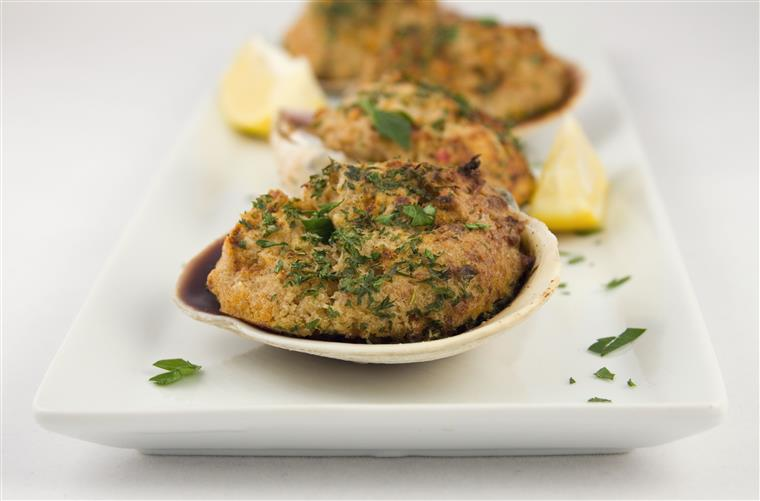 Stuffed crab cakes in shell lined up on white plate
