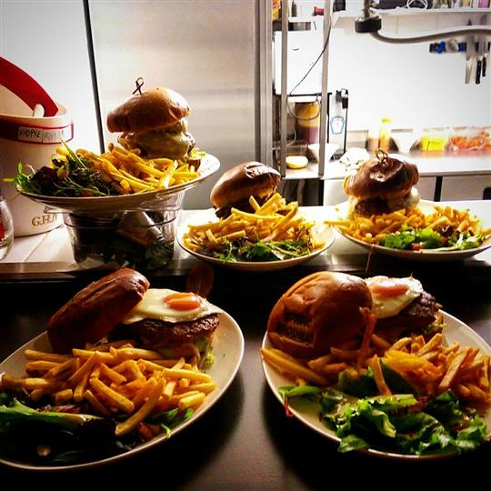 Several dishes of burgers topped with fried eggs served with french fries and side salad