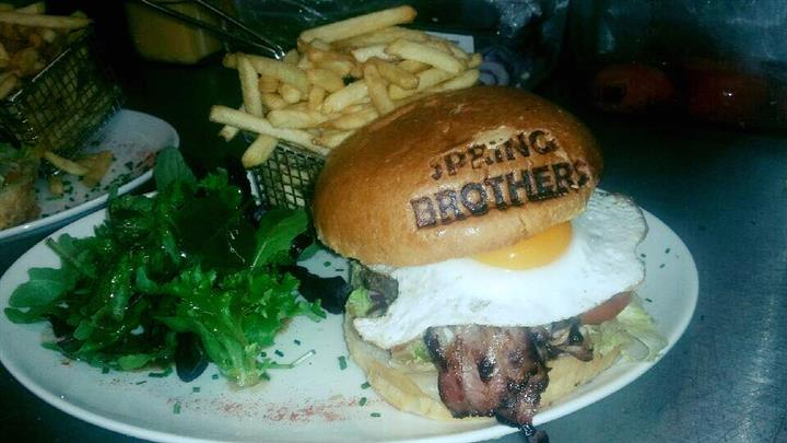 A burger topped with bacon and a fried egg with french fries