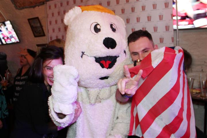 A couple with a man in a white bear suit posing for a photo