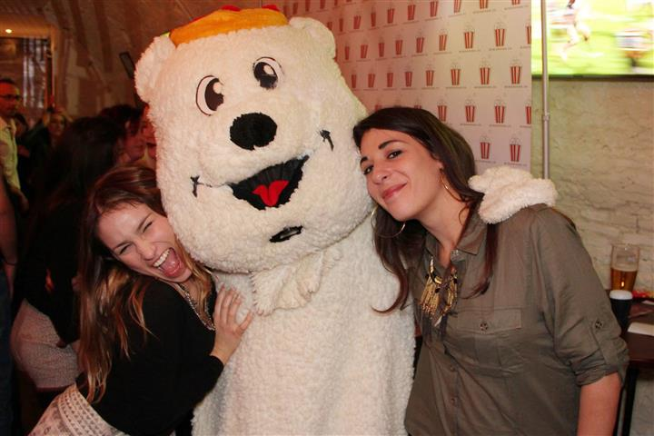 Two young ladies with a man in a white bear suit posing for a photo