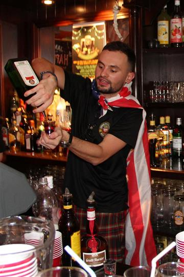 The barman serving a drink shot with a flag on his shoulders