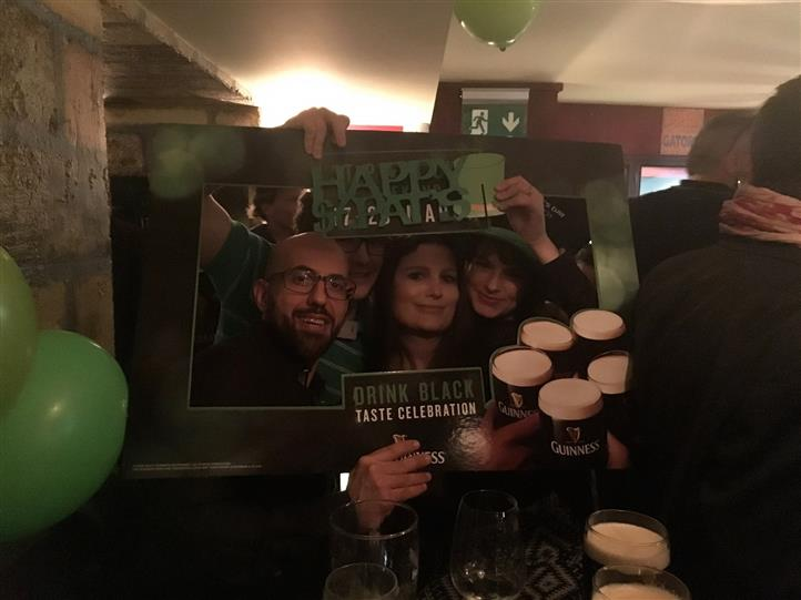 Two smiling couples posing for a photo holding a St. Patrick's picture frame