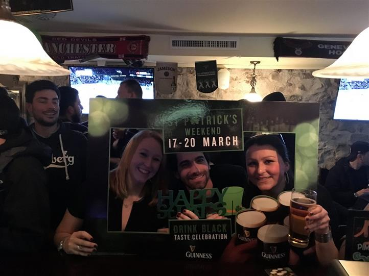Two smiling women and a man posing holding a St. Patrick's picture frame
