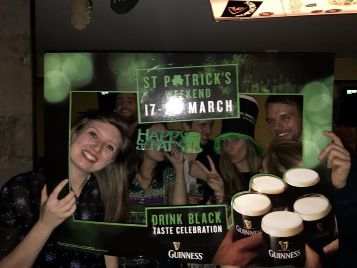 Six smiling people posing holding a St. Patrick's picture frame