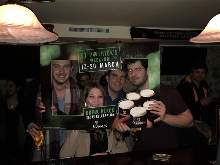 Three smiling men and a woman posing for a photo holding a  St. Patrick's weekend picture frame