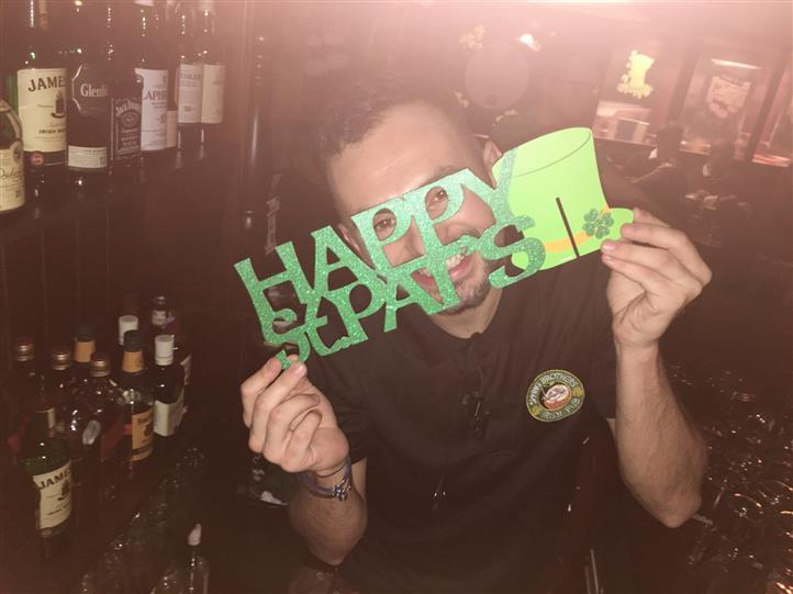 """A man at the bar holding a """"Happy St. Pat's"""" frame"""