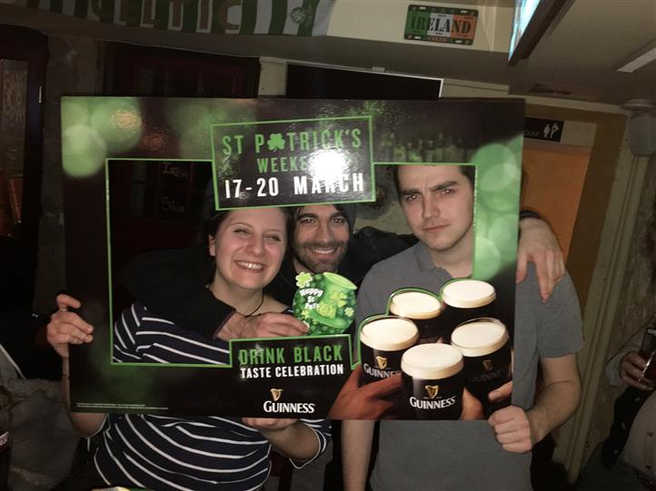 Two smiling men and a woman posing for a photo holding a  St. Patrick's weekend picture frame