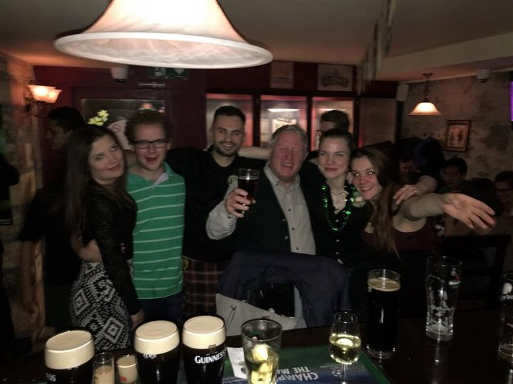 6 smiling people at the bar posing for a photo in front of glasses of drinks