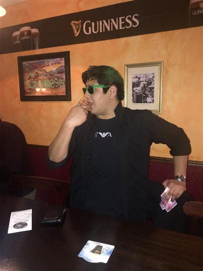 A man waring black clothes standing at the bar