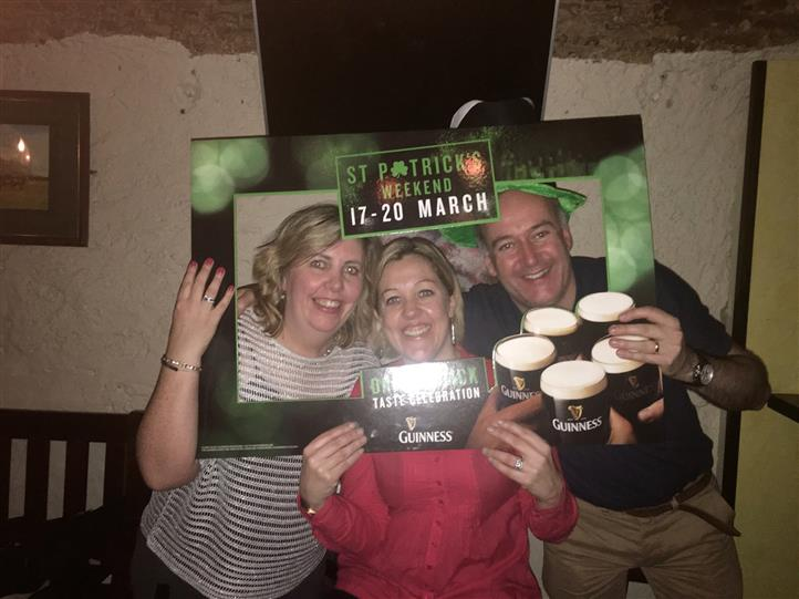 Two women and a man posing for a photo holding a St. Patrick's picture frame