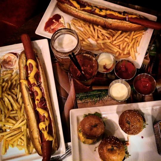 Two dishes of hot dogs one dish of sliders served with french fries