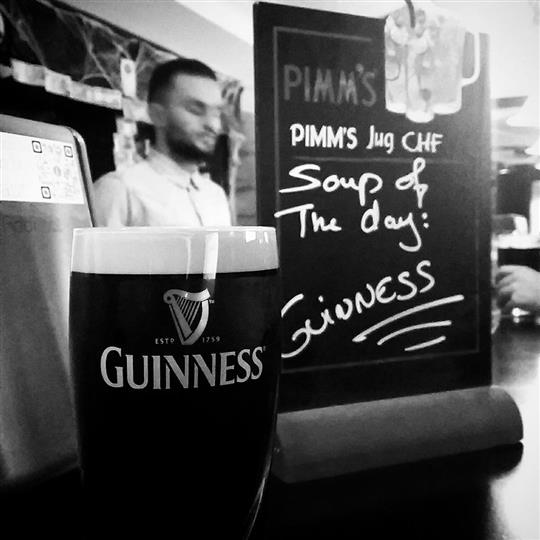 A glass of guinness beer next to a board at the bar