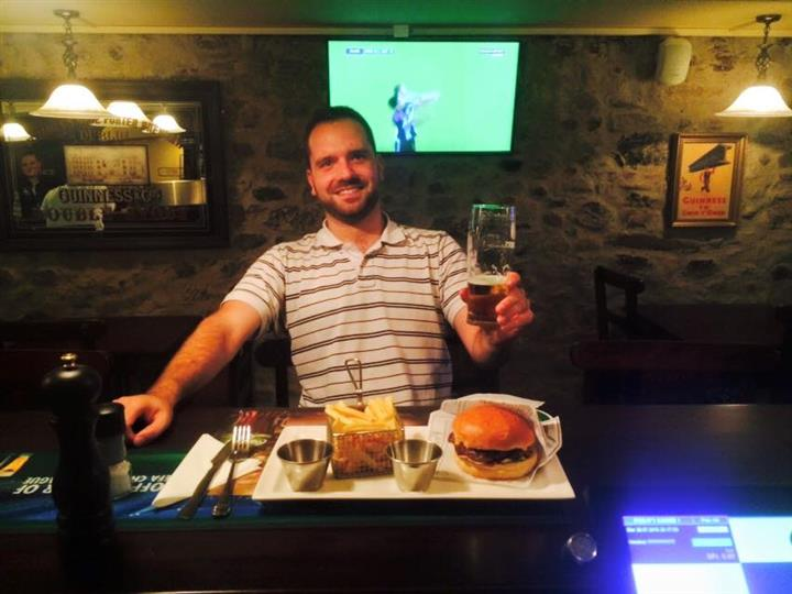 A smiling customer holding a beer in front of his burger and fries posing for a photo