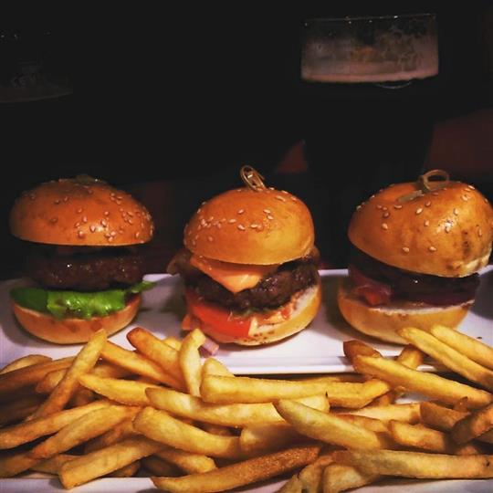 Three sliders served with french fries