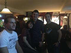 Four smiling people at the bar posing for a photo