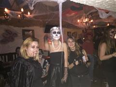 Three smiling ladies in Halloween shuits posing for a photo