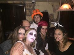 Six smiling guys in Halloween shuits posing for a photo
