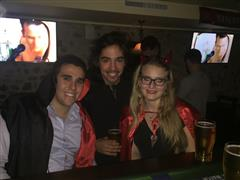 3 gys in Halloween suits posing for photo in the pub