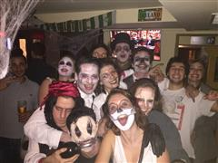 Smiling people in Halloween suits posing for photo in the pub