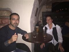 Two guys with drinks posing for a photo at a bar's table