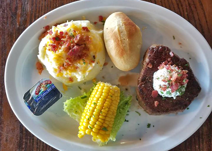 fillet mignon steak with mashed potatoes, corn on the cobb and a dinner roll