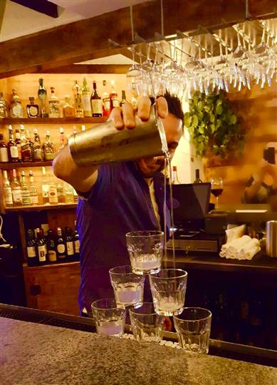bartender pouring drink into pyramid of shot glasses