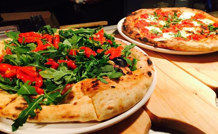 two pizzas with spinach and tomatoes