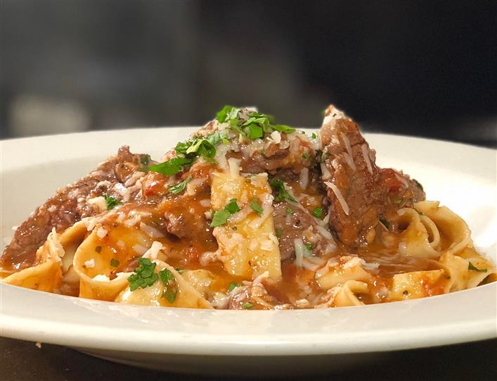 steak over pasta with sauce and shredded cheese
