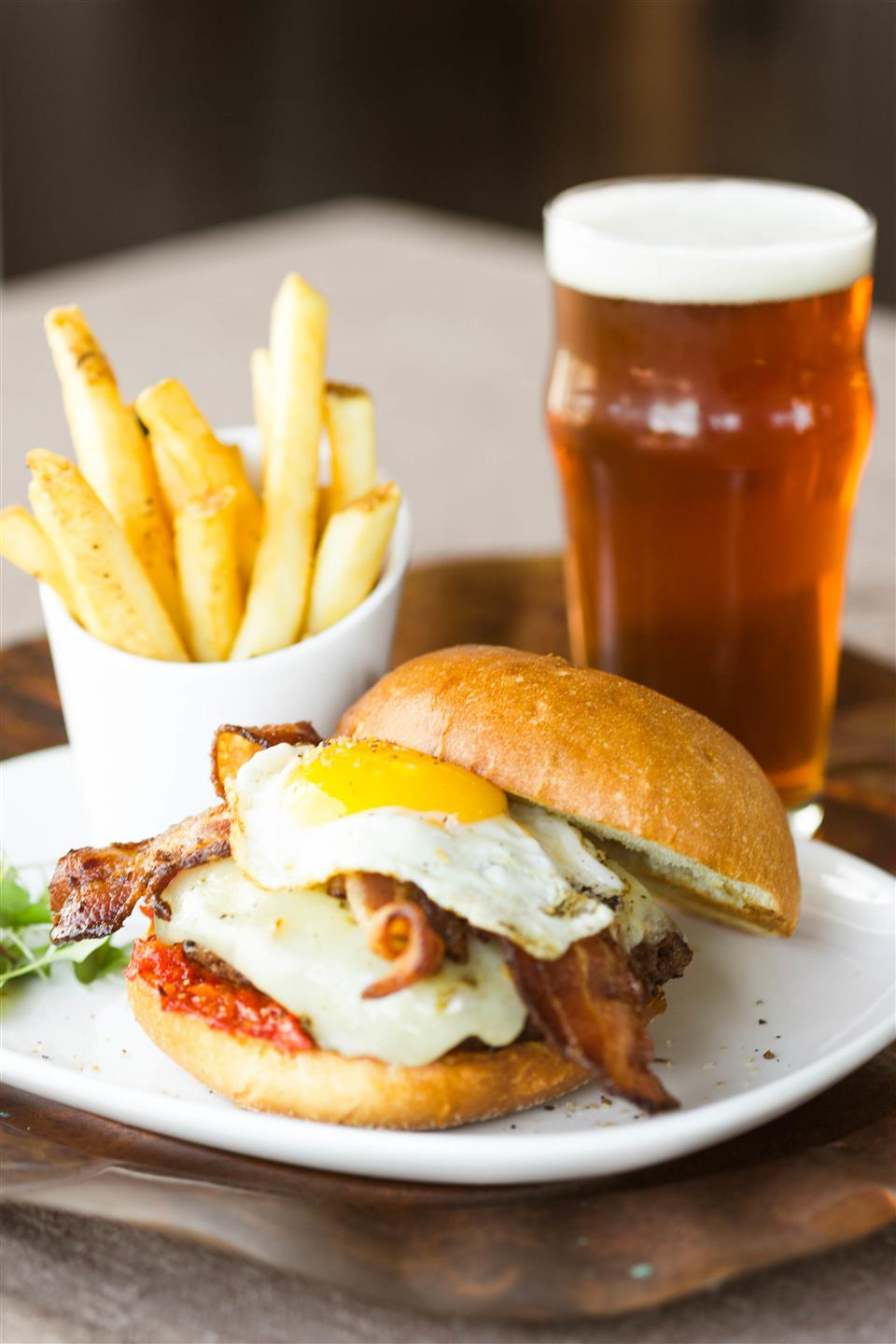 sandwich topped with an egg and bacon with fries and a glass of beer