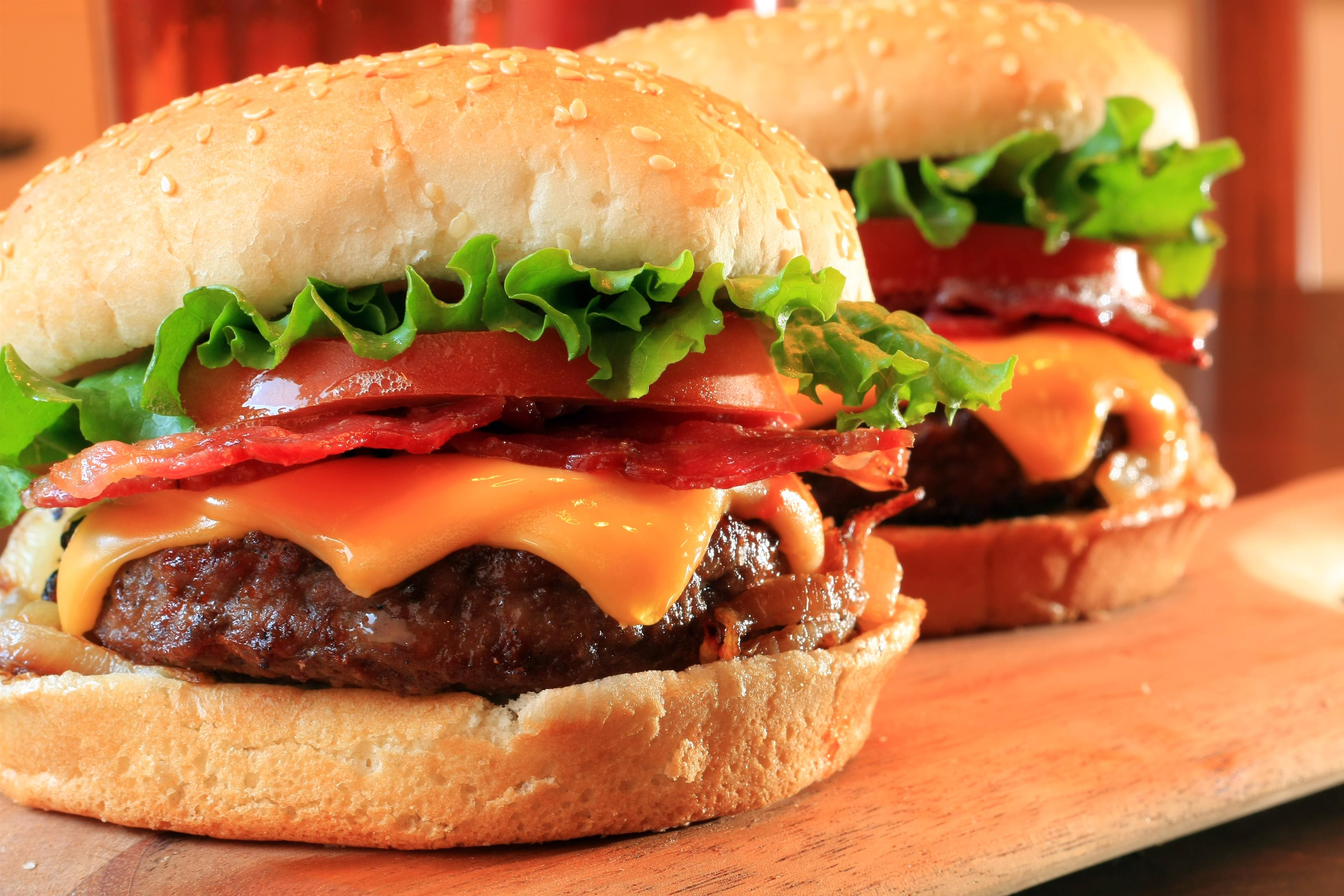 Two bacon cheeseburgers with tomato and lettuce on bun.