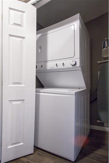Washer - dryer unit in room next to door