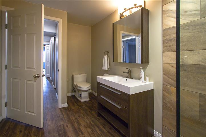 Bathroom with sink, mirror, toilet and open door leading to hallway
