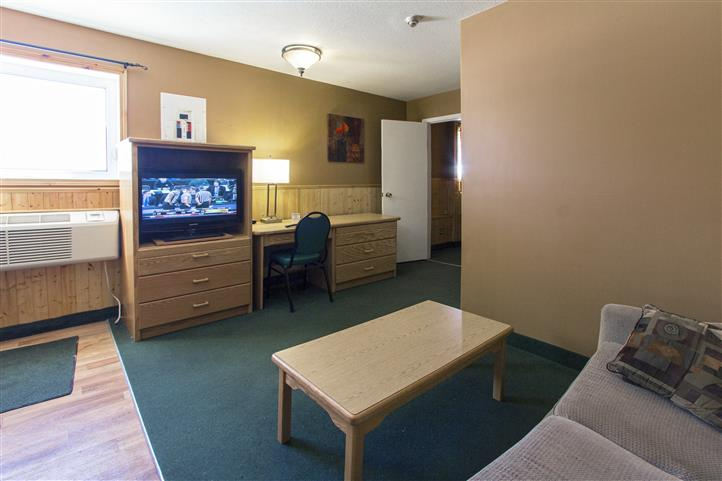 Room with couch, coffee table, dresser with television, desk with lamp and chair next to wall unit air conditioner.