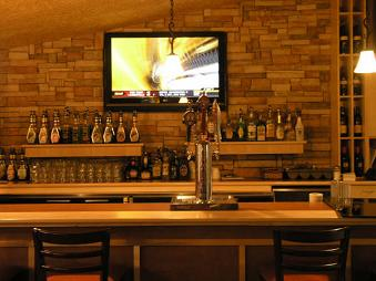 Bar with beer taps, liquor shelves and tv on wall