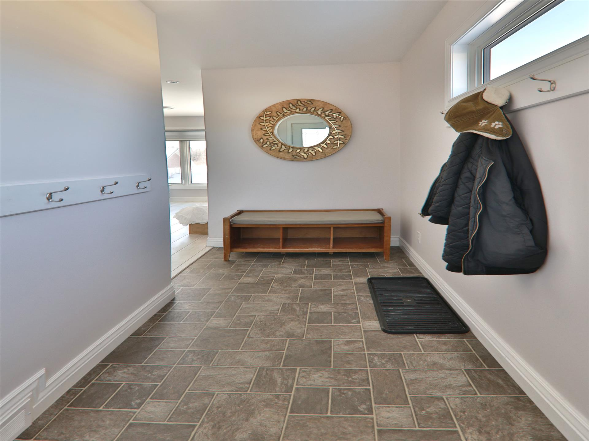 Entry way with coat hooks on the wall, a mirror and a bench