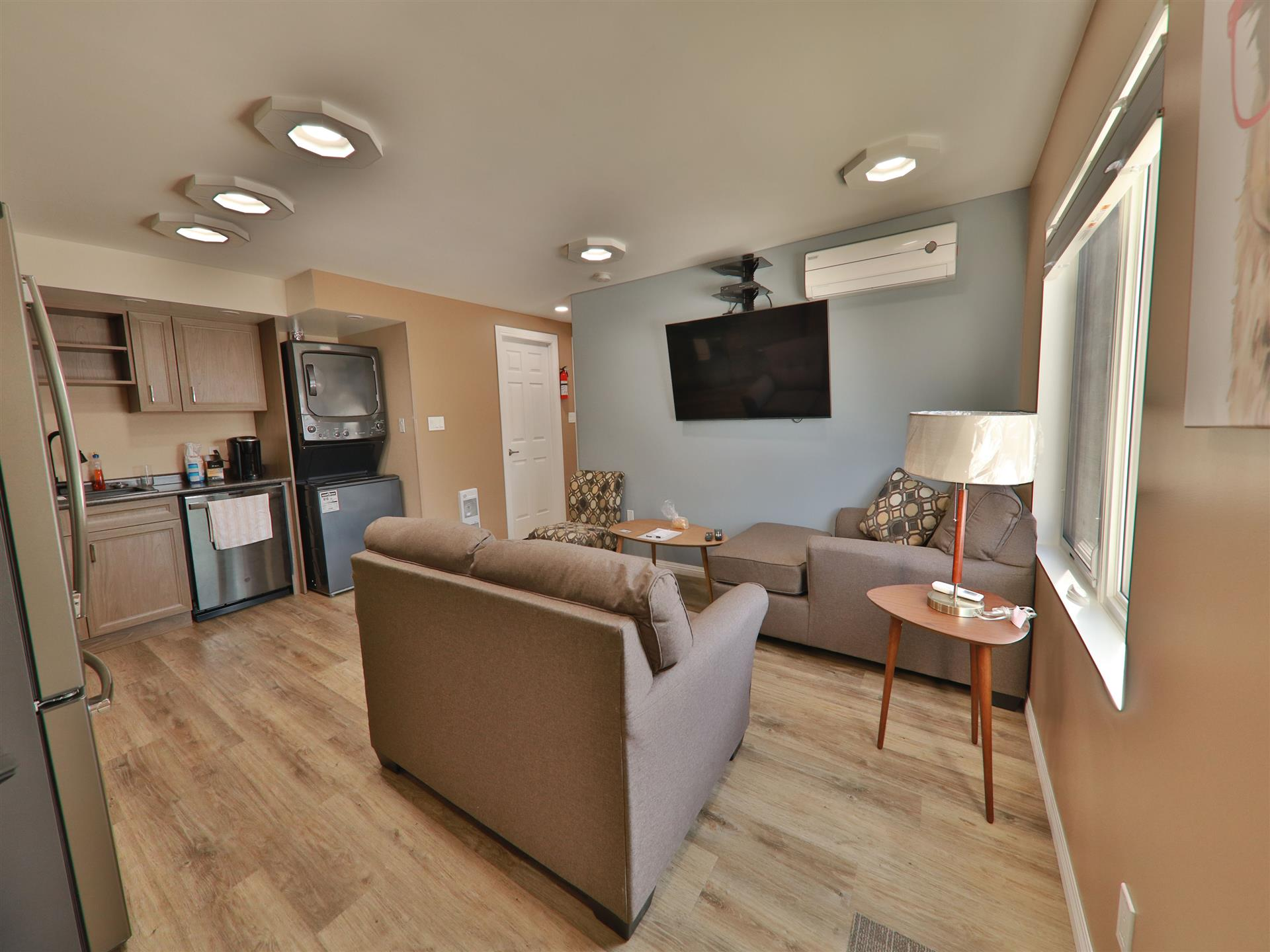Living area with kitchen, TV mounted and couchs