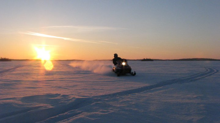 Snowmobiler on trail in front of sunset