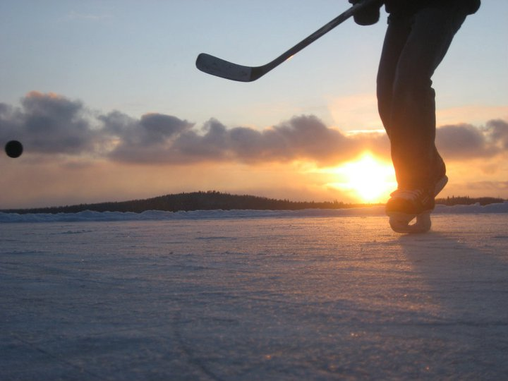 Low-angle shot of person playing hockey on ice in front of sunset