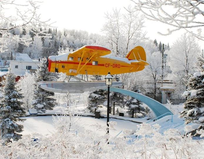 Elevated sea plane on display near snow-covered trees