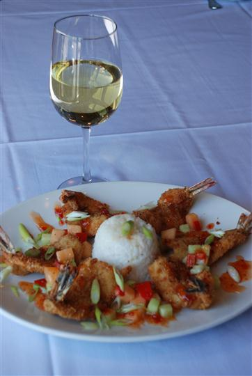 Fish served with white rice and diced veggies. Champagne in a glass beside the platter