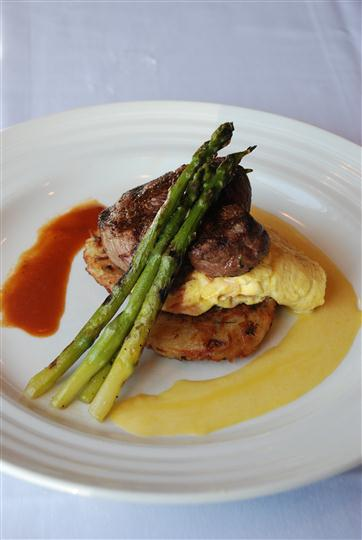 Steak and scrambled eggs topped with asparagus and 2 specialty sauces