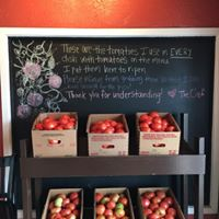 Tomatoes in baskets under a chalkboard sign