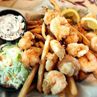 Fried shrimp with lemon slices and french fries