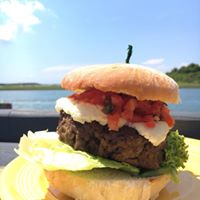 Burger with cheese, tomatoes, and lettuce in front of a river
