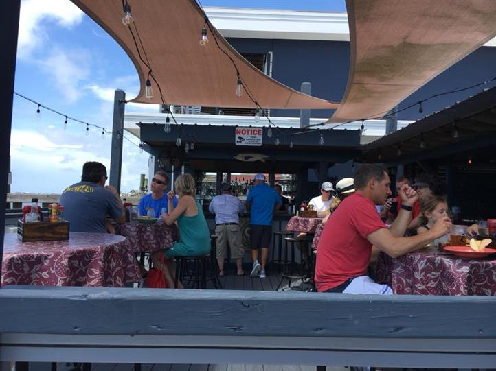 People dining on a patio next to a outdoor bar