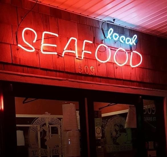 "a neon sign that says ""local seafood"""